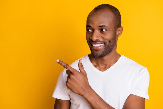 Крупный план его симпатичного привлекательного веселого веселого парня, демонстрирующего рекламное решение для копирования пространства, например, подписаться на подписку, изолированное на ярком ярком фоне яркого желтого цвета