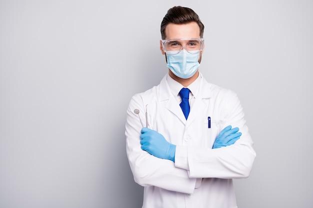 Крупным планом портрет его приятный привлекательный веселый опытный врач-стоматолог, держащий в руках стальные инструменты стоматологический центр, изолированный на светло-белом сером пастельном цвете