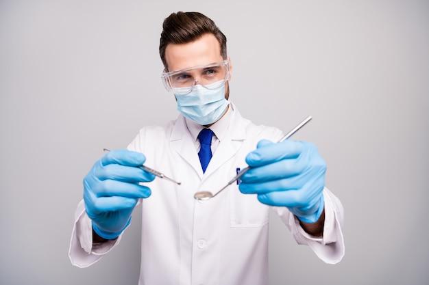 Крупный план его красивого привлекательного опытного квалифицированного стоматолога-стоматолога, держащего в руках стальной инструмент, готовящийся к операции, изолированный на светло-белом сером пастельном цвете