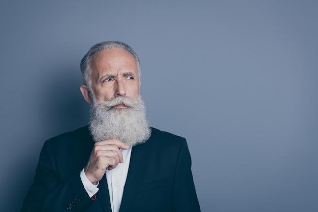 Портрет крупным планом его симпатичного привлекательного сосредоточенного подозрительного седого человека, гадающего о стратегии, касающегося бороды, изолированного на сером пастельном цветном фоне