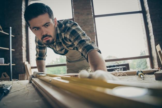 Крупный план его симпатичного привлекательного серьезного сосредоточенного трудолюбивого специалиста по ремонту, проверяющего гладкость доски, создавая стартовый проект нового дома в современном интерьере в стиле индустриального лофта