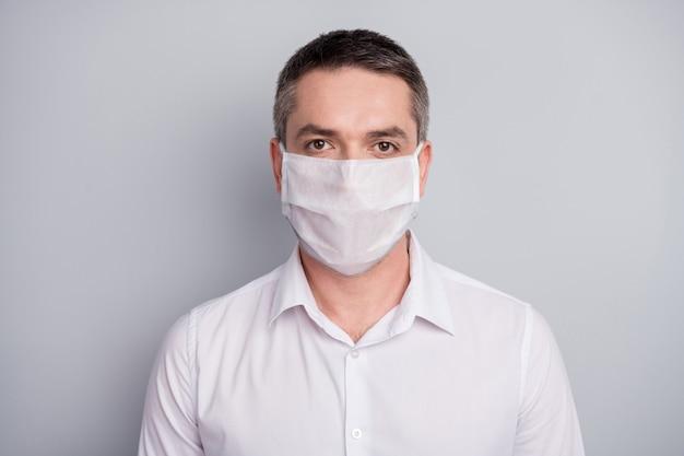 안전 마스크를 쓴 그의 멋지고 진지한 성숙한 남자의 클로즈 업 초상화는 바이러스성 폐렴 오염 중국 우한 질병을 막는 밝은 회색 파스텔 색상 배경