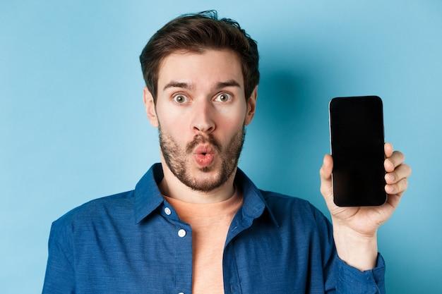Крупным планом портрет впечатленного человека сказать ничего себе, показывая пустой экран мобильного телефона, стоя на синем фоне.