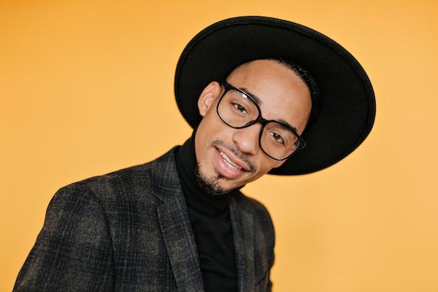 최신 유행 안경에 관심이 아프리카 남자의 클로즈업 초상화. 오렌지 벽에 웃 고 매혹적인 흑인 남자의 실내 사진.