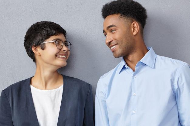 正式に服を着た異人種間のビジネスカップルの肖像画を閉じる