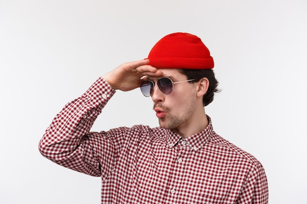 Крупным планом портрет заинтригованного и возбужденного молодого парня в битниках, замаскированном, в солнечных очках и красной шапочке, смотрящих вдаль, видя что-то очень крутое вдали, удивляясь на белой стене