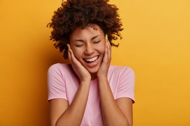 うれしそうな縮れ毛の女性のクローズアップの肖像画は頬に触れ、誠実な前向きな笑顔を持って、目を閉じて面白がって、陽気な何かから笑い、カジュアルな服を着て、黄色の壁に隔離されています