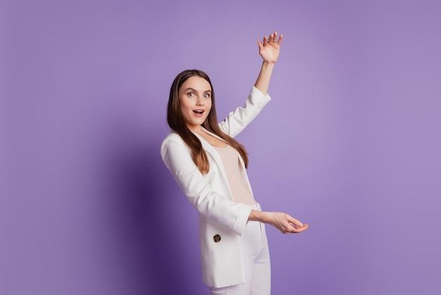 Крупным планом портрет дамы руки держат невидимый объект пустое пространство носить формальный костюм позирует на фиолетовой стене