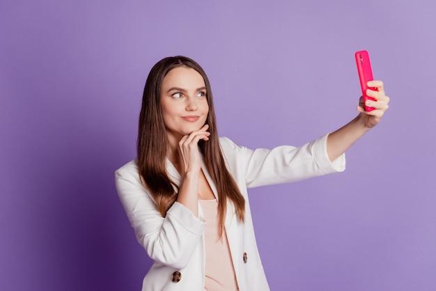 女性の肖像画をクローズアップ携帯電話を取る紫の壁にポーズをとって自分撮りを着るフォーマルなスーツ