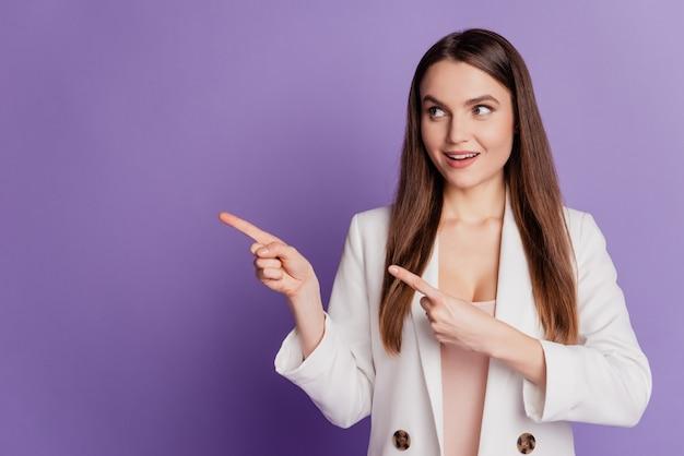 女性のクローズアップの肖像画は、指の空きスペースを示すサイドウェアのフォーマルなスーツを紫色の壁にポーズをとる
