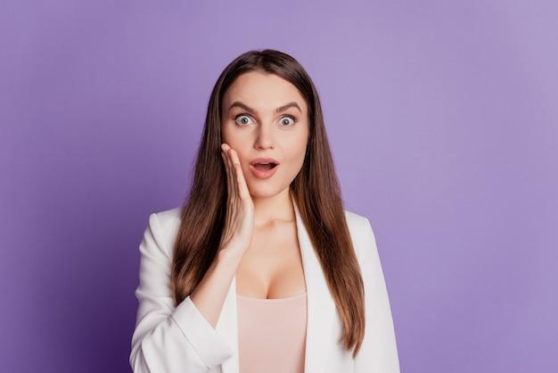 女性の驚いた顔の手のひらの頬の開いた口を着用して紫色の壁にポーズをとるフォーマルなスーツの肖像画をクローズアップ