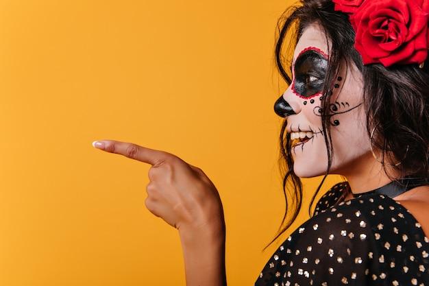 좀비 메이크업 라틴 갈색 머리 여자의 클로즈업 초상화. 할로윈을 축 하하는 muerte 복장에 매력적인 검은 머리 소녀.