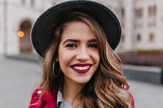 도시 주변을 산책하는 동안 포즈를 취하는 붉은 입술으로 웃는 금발의 여자의 클로즈 업 초상화