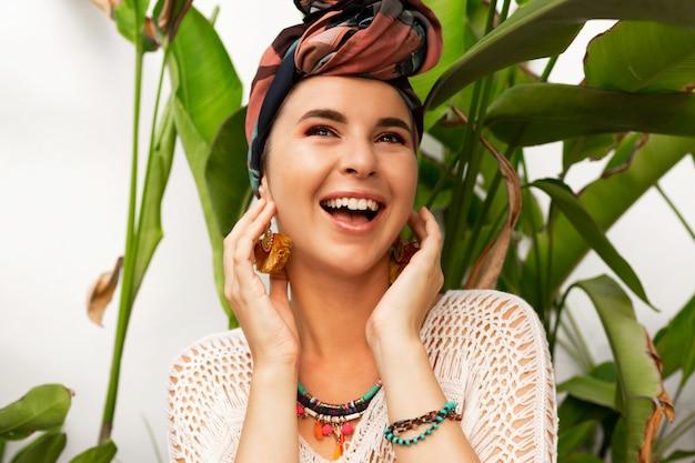 ヤシの木にポーズの頭の上のターバンと笑う女性のポートレートを閉じます