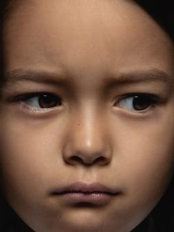 Закройте вверх по портрету маленькой и эмоциональной азиатской девушки. детализированная фотосессия девушки-модели с ухоженной кожей и ярким выражением лица. понятие о человеческих эмоциях. выглядит грустно, расстроено.