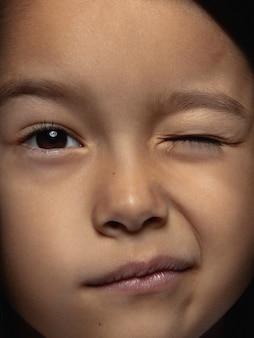 Закройте вверх по портрету маленькой и эмоциональной азиатской девушки. детализированная фотосессия девушки-модели с ухоженной кожей и ярким выражением лица. понятие о человеческих эмоциях. подмигивает, игриво улыбается.