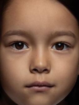 작고 감정적 인 아시아 여자의 초상화를 닫습니다. 잘 관리 된 피부와 밝은 표정으로 여성 모델의 매우 디테일 한 사진 촬영. 인간 감정의 개념. 카메라를 찾고 있습니다.