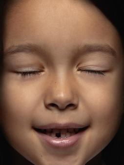 小さくて感情的なアジアの女の子の肖像画を閉じます。手入れの行き届いた肌と明るい表情の女性モデルの非常に詳細な写真撮影。人間の感情の概念。目を閉じて笑う。
