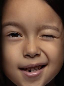 小さくて感情的なアジアの女の子の肖像画を閉じます。