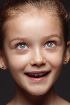 Закройте вверх по портрету маленькой и эмоциональной кавказской девушки. детализированная фотосессия девушки-модели с ухоженной кожей и ярким выражением лица. понятие о человеческих эмоциях. мечтать, смотреть вверх.