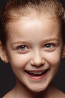 小さくて感情的な白人の女の子の肖像画を閉じます。手入れの行き届いた肌と明るい表情の女性モデルの非常に詳細な写真撮影。人間の感情の概念。笑って、笑って。