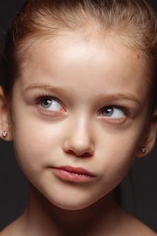 小さくて感情的な白人の女の子の肖像画を閉じます。手入れの行き届いた肌と明るい表情の女性モデルの非常に詳細な写真撮影。人間の感情の概念。思慮深く、考えています。