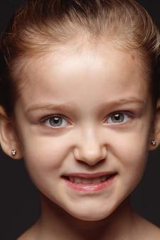 Закройте вверх по портрету маленькой и эмоциональной кавказской девушки. детализированная фотосессия девушки-модели с ухоженной кожей и ярким выражением лица. понятие о человеческих эмоциях. злой, агрессивный.