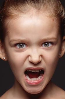 小さくて感情的な白人の女の子の肖像画を閉じます。手入れの行き届いた肌と明るい表情の女性モデルの非常に詳細な写真撮影。人間の感情の概念。怒り、攻撃的。