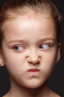 Закройте вверх по портрету маленькой и эмоциональной кавказской девушки. детализированная фотосессия девушки-модели с ухоженной кожей и ярким выражением лица. понятие о человеческих эмоциях. злой, мрачный.
