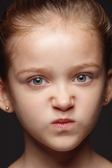 小さくて感情的な白人の女の子の肖像画を閉じます。手入れの行き届いた肌と明るい表情の女性モデルの非常に詳細な写真撮影。人間の感情の概念。怒って、憂鬱。