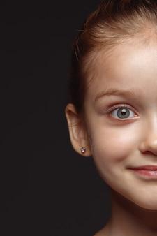 작고 감정적 인 백인 여자의 초상화를 닫습니다. 잘 관리 된 피부와 밝은 표정으로 여성 모델의 매우 디테일 한 사진 촬영. 인간 감정의 개념. 차분한 미소.