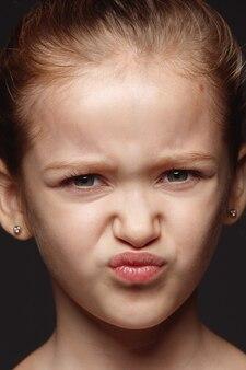 Закройте вверх по портрету маленькой и эмоциональной кавказской девушки. детализированная фотосессия девушки-модели с ухоженной кожей и ярким выражением лица. понятие о человеческих эмоциях. отвратительно.