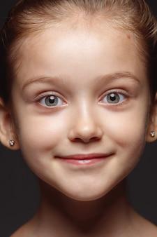 小さくて感情的な白人の女の子の肖像画を閉じます。手入れの行き届いた肌と明るい表情の女性モデルの非常に詳細な写真撮影。人間の感情の概念。カメラを見てください。