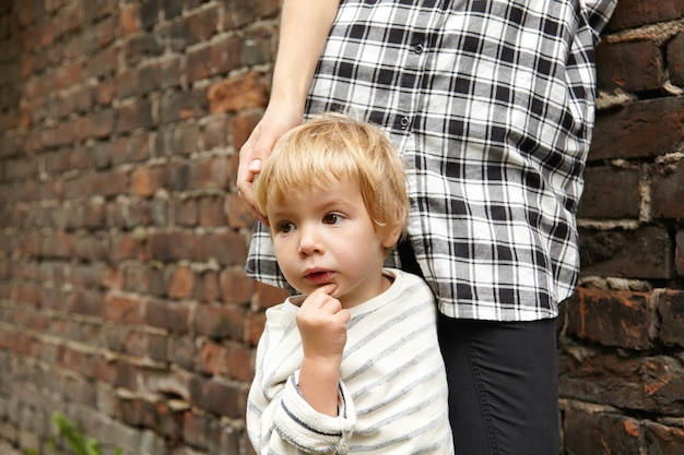 小さな金髪の子供とレンガの壁の近くの彼の母親のクローズアップの肖像画。物思いに沈んだ男の子の画像と、チェックのシャツとズボンを着た愛するママの姿。家族が街の裏通りを散歩します。