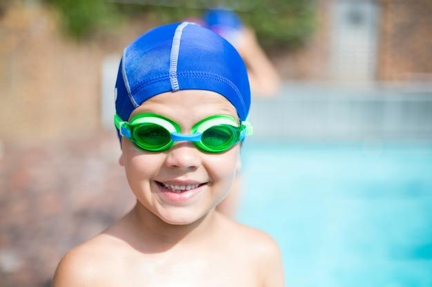 수영장에서 수영 고글과 모자를 쓰고 어린 소년의 초상화를 닫습니다