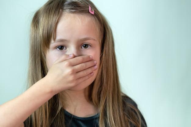 손으로 그녀의 입을 덮고 긴 머리를 가진 작은 아이 소녀의 클로즈 업 초상화.