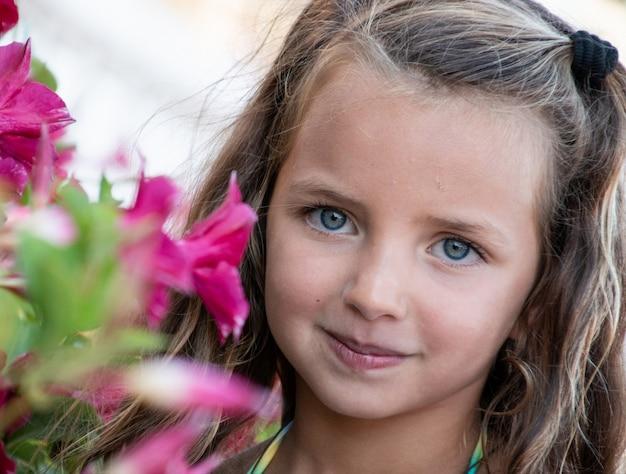 꽃과 함께 작은 귀여운 소녀의 초상화를 닫습니다