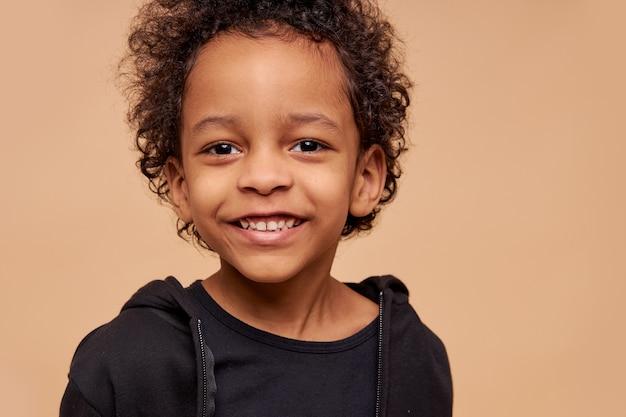 孤立した小さな浅黒い肌の少年の肖像画をクローズアップ
