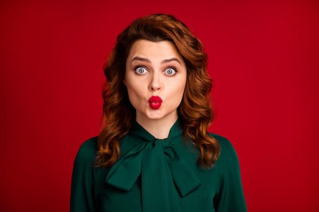 鮮やかな赤い背景の上に分離されたエアキスを送信する愛らしいウェーブのかかった髪の少女のクローズアップの肖像画