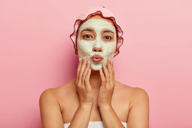 화장품 페이셜 마스크로 사랑스러운 아시아 여성의 초상화를 닫고, 얼굴을 부드럽게 만지고, 입술을 접고, 직접 보며, 청결과 미용 치료를 즐깁니다. 피부 관리 루틴