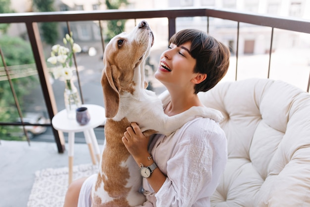 バルコニーに座っている間面白い子犬を笑顔で見ている素敵な黒髪の女性のクローズアップの肖像画。バスローブを着た見事な女の子は、ビーグル犬と遊ぶブレスレットと腕時計を身に着けています