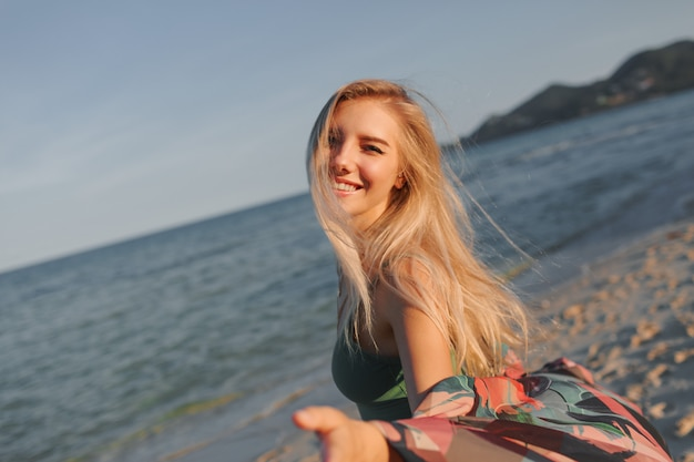 ビーチの上を歩く素敵なブロンドのヨーロッパの女性の肖像画を閉じます。