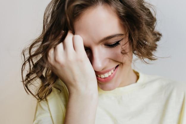 恥ずかしがり屋の笑顔でポーズをとる素敵な白人の女の子のクローズアップの肖像画。短い髪の女性が顔に触れて目を閉じて笑っている室内写真。