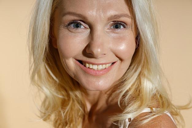 カメラに笑みを浮かべて自然なメイクで素敵な白人の成熟したブロンドの女性の肖像画をクローズアップ