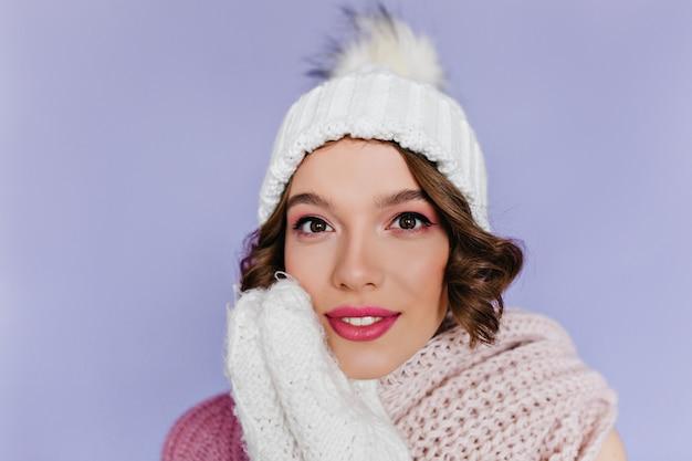 紫色の壁にポーズをとって白いウールの手袋で素敵なヨーロッパの女性のクローズアップの肖像画。ピンクの化粧をしたイケメンの女性の室内写真はかわいいニット帽をかぶっています。