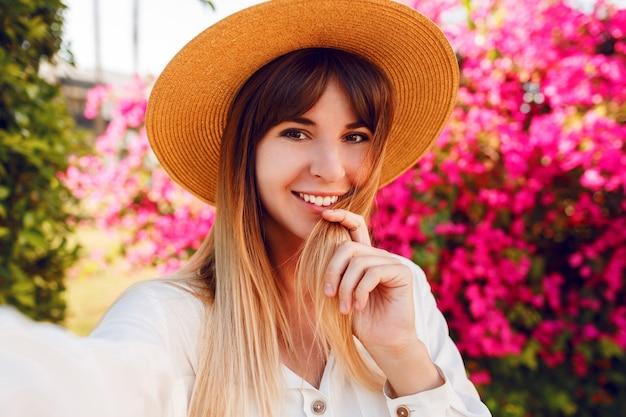 Крупным планом портрет прекрасной девушки в модной соломенной шляпе, делающей селфи портрет