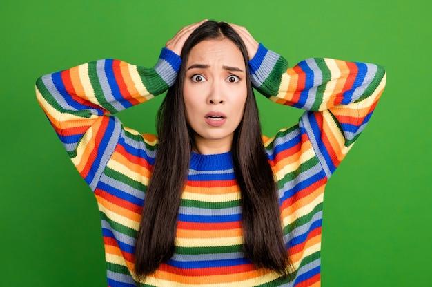 鮮やかな緑色の背景に分離された素敵な圧倒された心配している女の子の悪いニュースの反応のクローズアップの肖像画