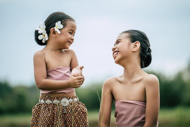 닫기, 태국 전통 드레스에 사랑스러운 여동생과 젊은 여동생의 초상화와 그녀의 귀에 흰 꽃을 넣고, 서로의 눈을 들여다보고 행복하게 웃습니다.