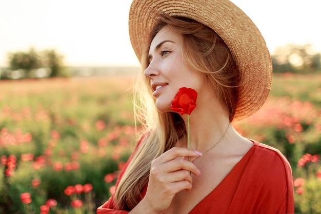 フィールドの背景にポーズをとって手にケシの花を持つ素敵なロマンチックな女性の肖像画を閉じます。麦わら帽子をかぶっています。柔らかな色。