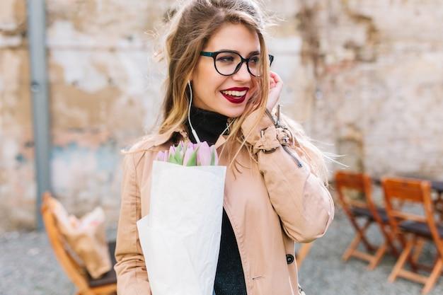 美しい花を保持している屋外カフェでの日付の素敵な若い女性のクローズアップの肖像画。チューリップの花束を持つ魅力的な女の子は、メガネを通して見回しているレストランで友人を待つ